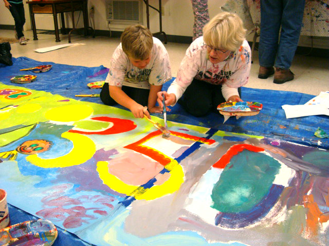 ArtVan kids and volunteer working on 350 banner